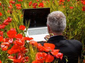 A man working in a laptop computer in a flowered garden.