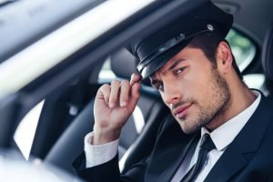 Portrait of a handsome male chauffeur sitting in a car and making saluting gesture