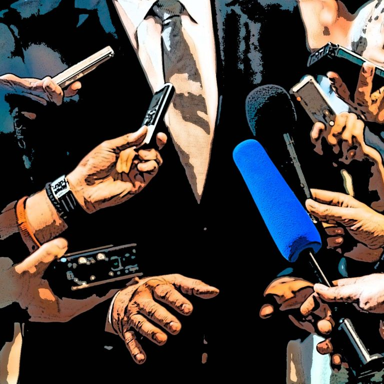 A man surrounded by microphones