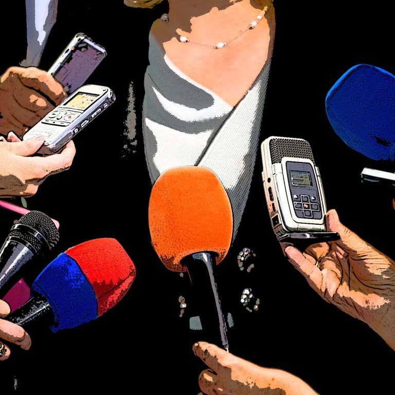 A woman surrounded by microphones