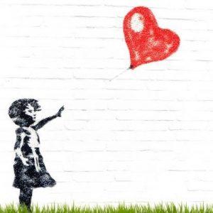 A girl releasing a heart shaped air balloon