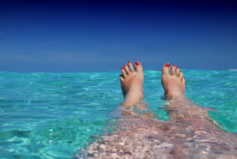 Legs and feet of a woman floating in a blue clear water